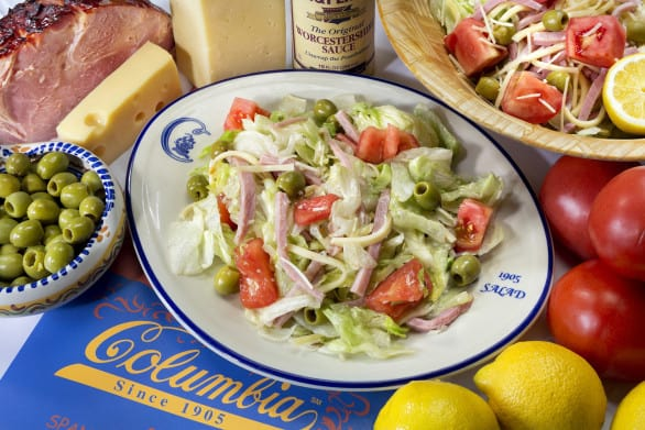"Columbia's Original 1905 Salad consists of iceberg lettuce with julienne of baked ham, natural Swiss cheese, tomato, olives, grated Romano cheese and their famous garlic dressing. The signature salad, named for the year the restaurant was founded in Tampa's Latin district of Ybor City, was inspired by immigrants to the Cigar City: Romano cheese from the Sicilians and the famous garlic dressing used by Cubans to marinate fresh roast pork, plus Florida tomatoes, iceberg lettuce*, julienne of baked ham and Swiss cheese. In the 40s, Tony Noriega, who ventured to New York City during the Depression to find work, added a ""secret ingredient,"" Worcestershire sauce, to the recipe."