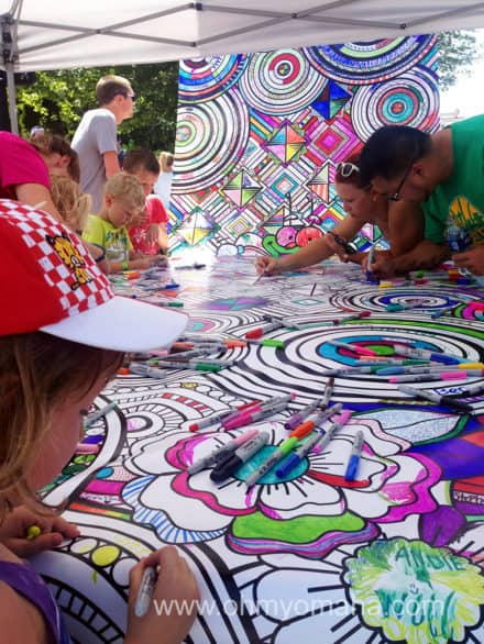 Mooch and fellow art lovers add to the community art project at the Des Moines Arts Festival.