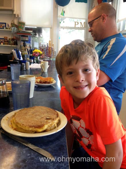 My son smiling before he realizes I'll require him to share his french pancakes.