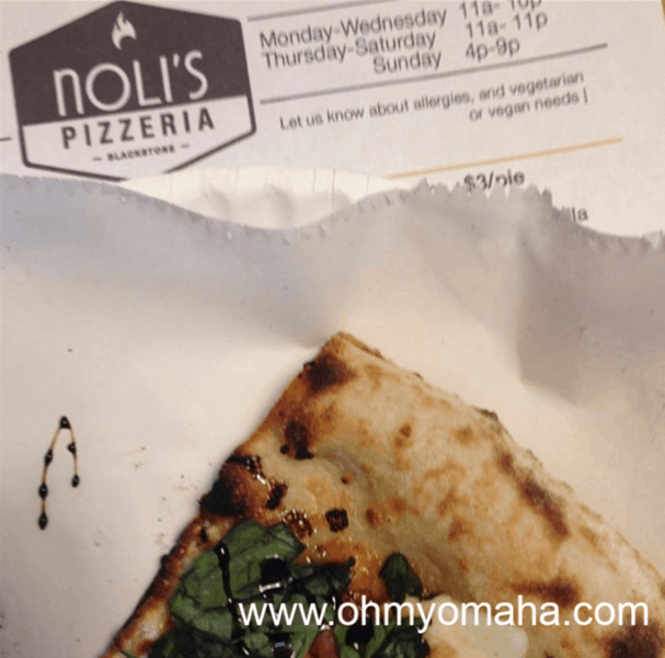 Slice of pizza and a menu at Noli's Pizzeria