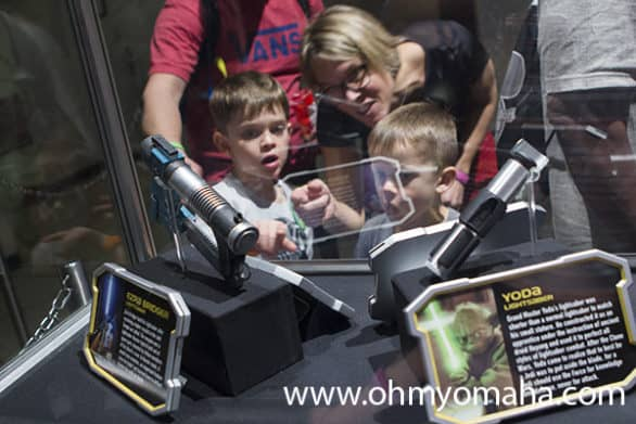 Family looking at light sabers on display at Hollywood Studios