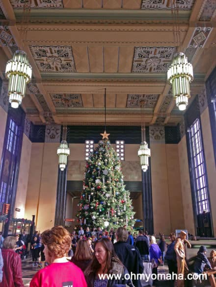 A crowd around the Christmas tree during Christmas at Union Station at The Durham Museum.