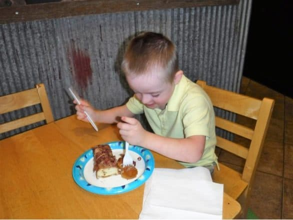 A boy eating the maple bacon long john at a kid's table at Flyboy Donuts in Sioux Falls, S.D.