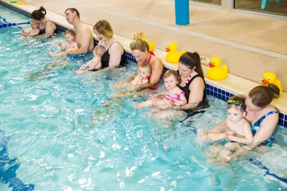 Parents with their babies at a swim class in a Goldfish Swim School pool