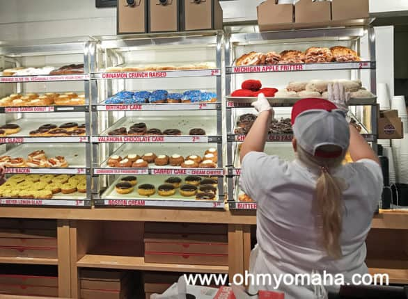 Employee adding more donuts to the display at Do-Rite Donuts in Chicago