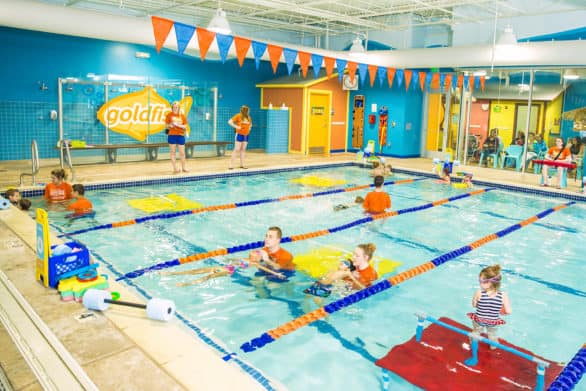 Swim lessons at Goldfish Swim School, with parents in the background.