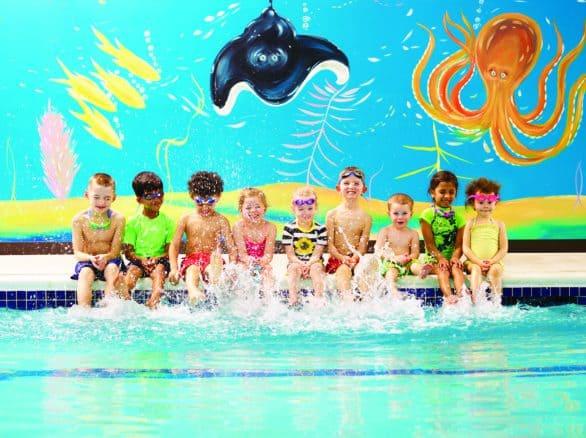 Group of kids splashing water with their feet at Goldfish Swim School pool