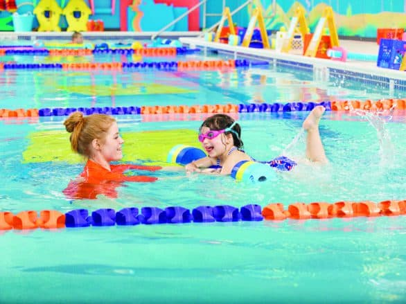 Student and instructor in the pool at Goldfish Swim School