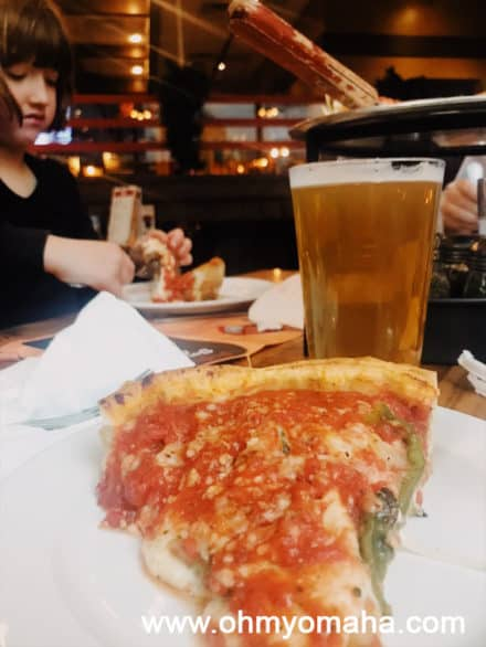 Giordano's deep dish pizza slice with a local beer