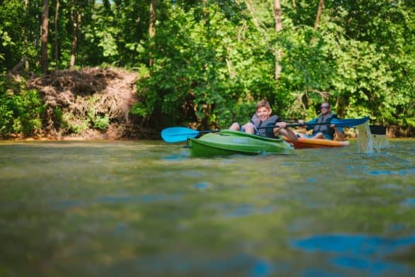 Two kayakers floating down the Current River, part of the Ozark National Scenic Riverway