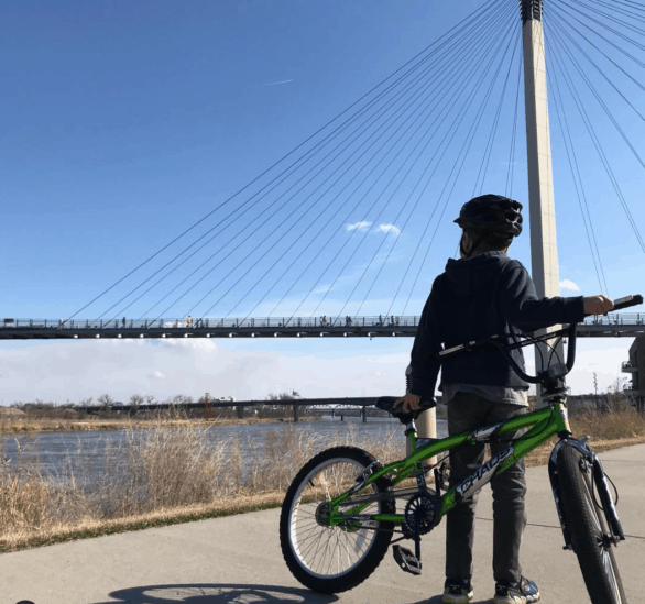 Kid by a bike with the Bob Kerrey Pedestrian Bridge and Missouri River in the background