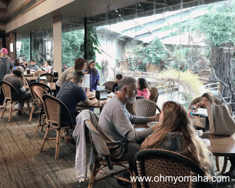 Diners at TreeTops Restaurant sitting at tables by the windows overlooking the indoor rainforest at Omaha's zoo