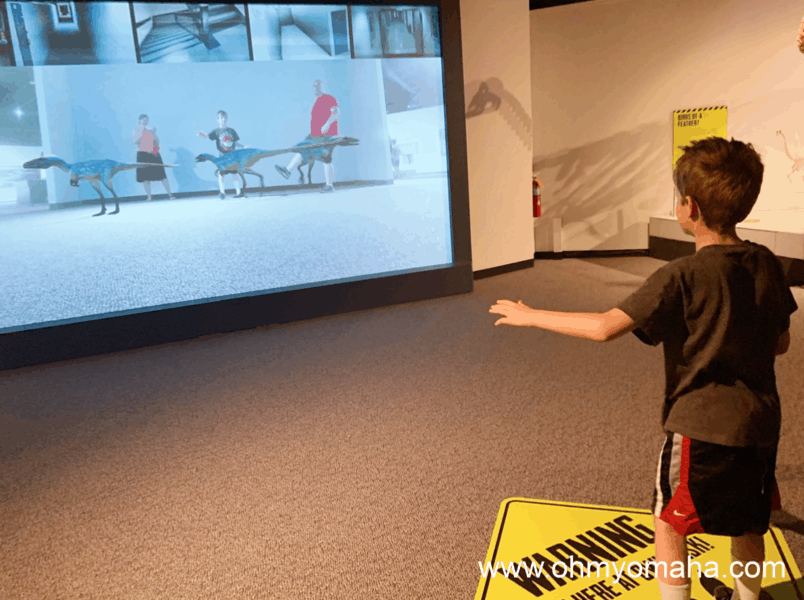 Interactive things to do in the summer exhibit at The Durham Museum - The augmented reality screen puts you in a scene with life-sized dinosaurs.