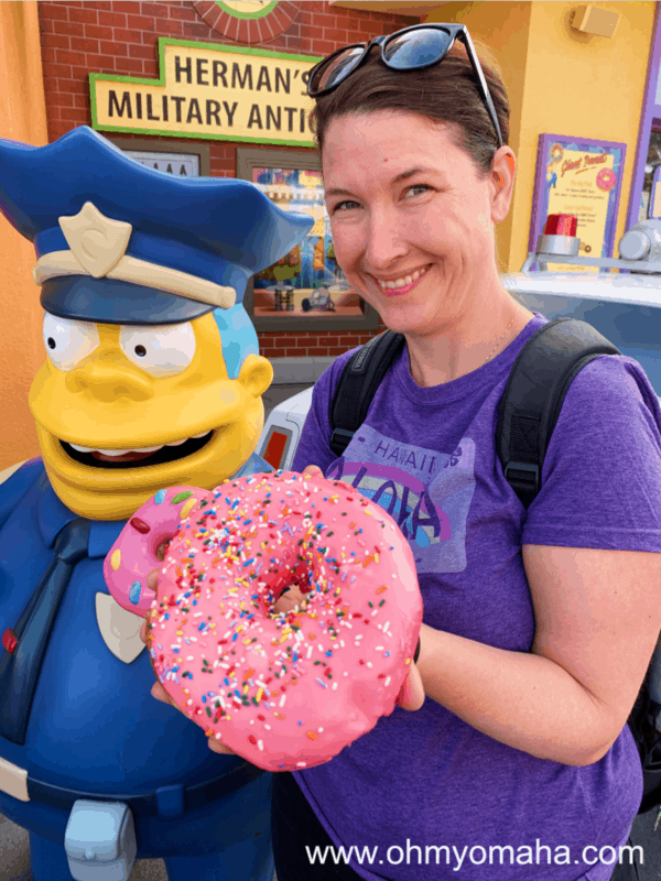 Kim and a giant pink frosted donut at Universal Studios Hollywood