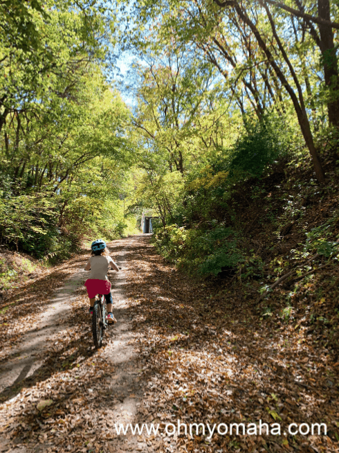 Girl riding a bike in the fall on the Wabash Trace Trail in Iowa