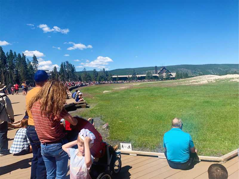 The crowd waiting for Old Faithful to erupt. There is a small sign in the background asking people to maintain 6 feet apart.