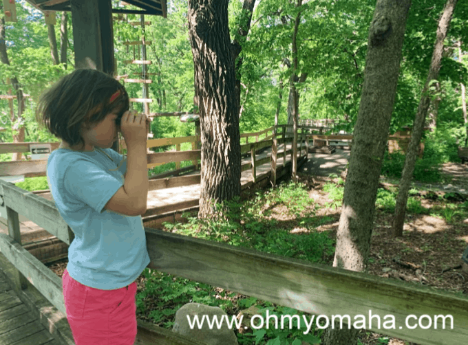 Girl using binoculars from the Family Backpack at Fontenelle Forest