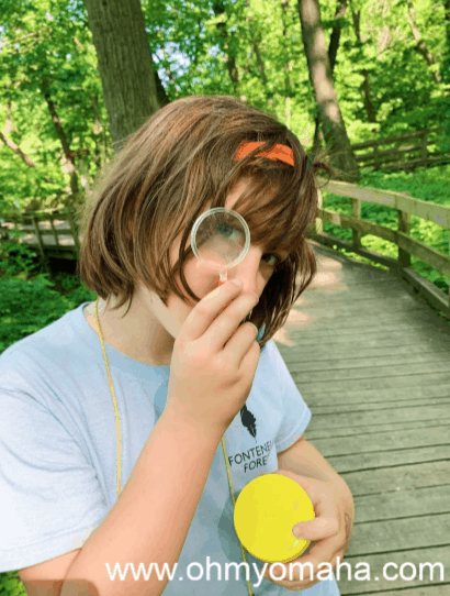 Girl with magnifying glass at Fontenelle Forest