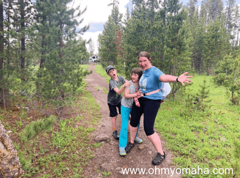 Family smiling after a rain-soaked hike in Yellowstone.