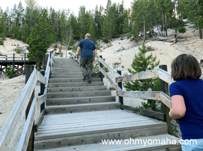 Dad and daughter walking up stairs at Mud Volcano trail in Yellowstone National Park.