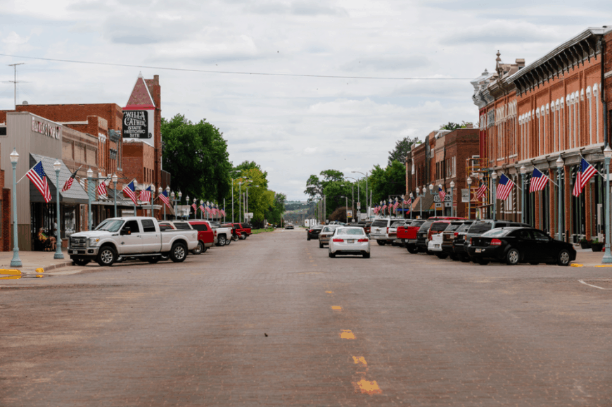 A view of downtown Red Cloud, Nebraska. You can see the sign for the Willa Cather State Historic Site on a building on the lefthand side of the road.