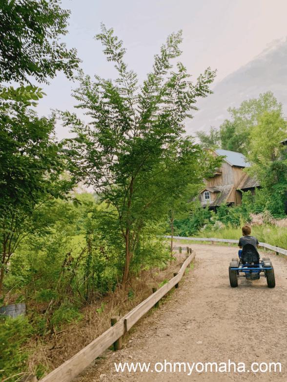 Boy riding a pedal cart at Vala's Pumpkin Patch in Grenta, Nebraska.