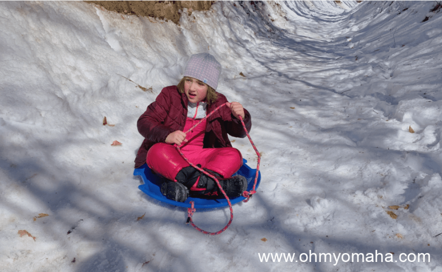 Girl sledding near Omaha in the winter