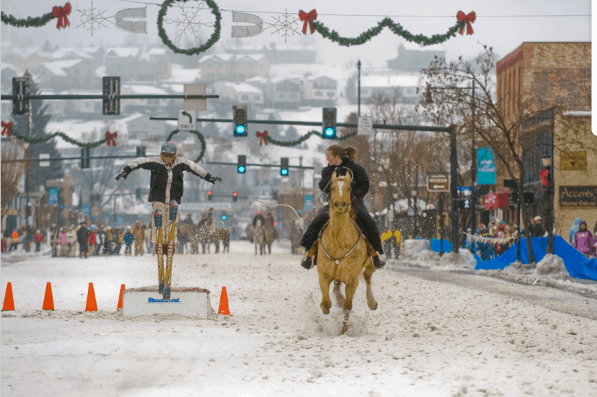 Spotting a landing during a skijoring jump down one of Steamboat's main streets.