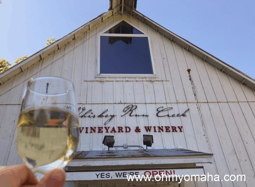 A glass of white wine in front of Whiskey Run Creek Vineyard & Winery in Brownville, Nebraska.