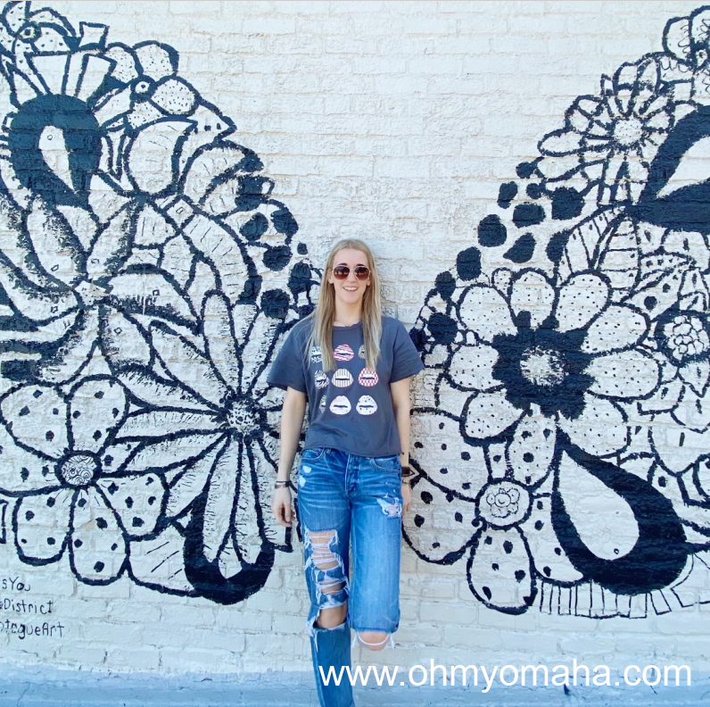 Girl in front of a mural in the Blackstone District in Omaha