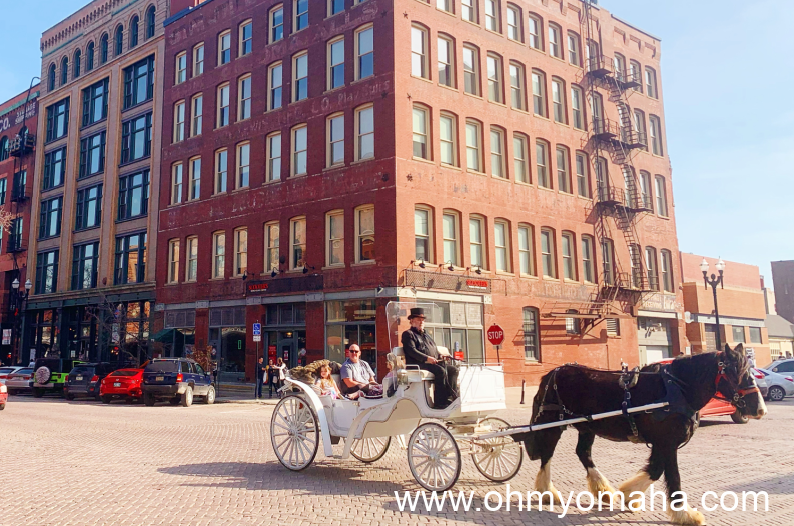 A horse-drawn carriage on an Old Market brick road.