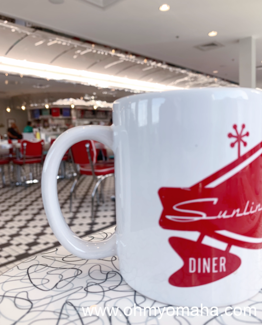 A cup of coffee with the background of the 1950s-themed diner, Sunliner Diner in Gulf Shores, Alabama.