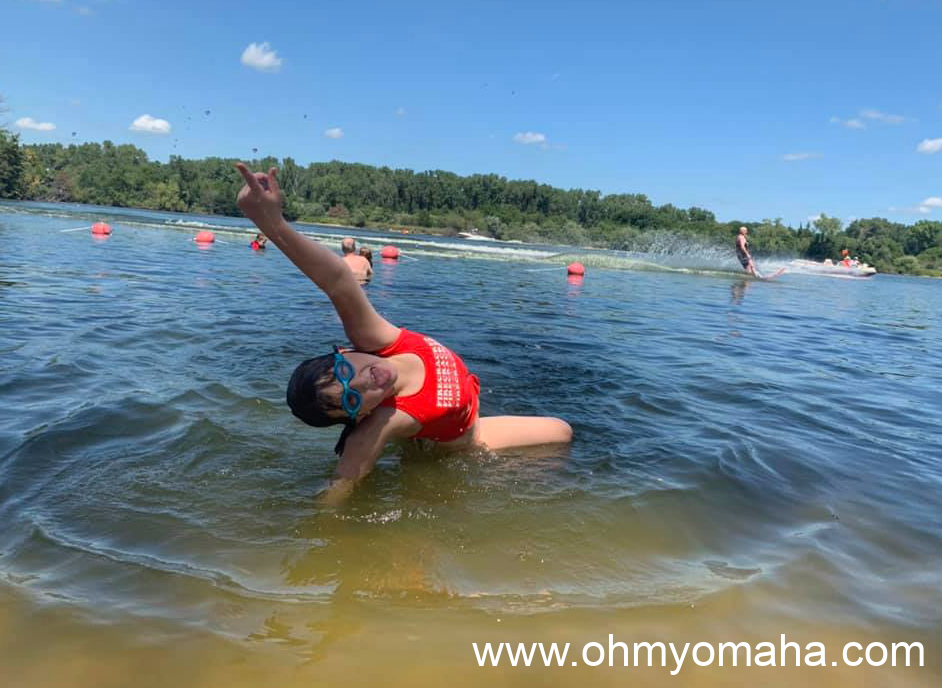 Girl playing in the water with a water-skier behind her at a lake in Fremont, Nebraska.