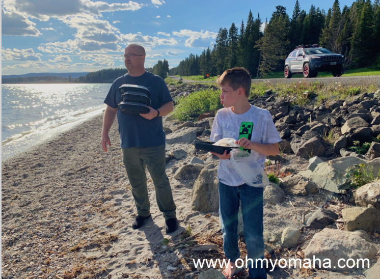 dad and son having a picnic dinner on the rocky beach of Yellowstone Lake