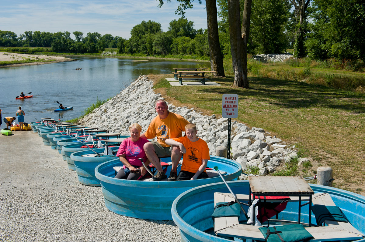 A family seated in a blue tank at Tank Down the River by the Elkhorn River