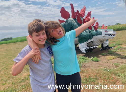 Two kids pose in front of a stegosaurus sculpture in Akron, Iowa