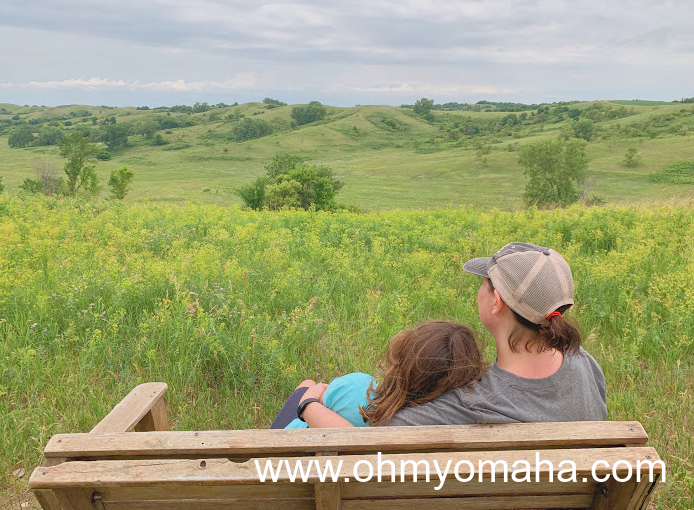 Mom and daughter on a bench overlooking the Broken Kettle Grasslands, a prairie in the Loess Hills