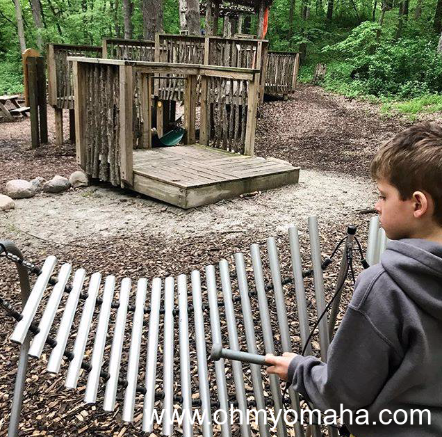 Boy playing the xylophone at the nature playscape at Dorothy Pecaut Nature Center in Sioux City