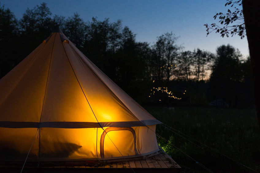 Glamping bell tent glows at night at forest