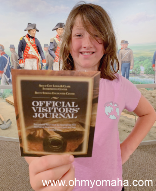 Girl holding a journal for stamping at the Lewis & Clark Interpretive Center
