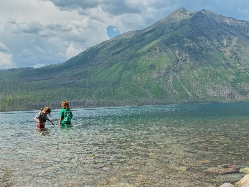 Girls wading in the water of Lake McDonald