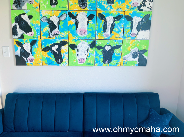 A sofa and cow art at New Day Dairy GuestBarn in Iowa