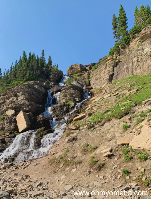 A waterfall seen from the road while driving Going-to-the-Sun Road.