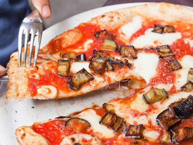 Serving a slice of Neapolitan pizza
